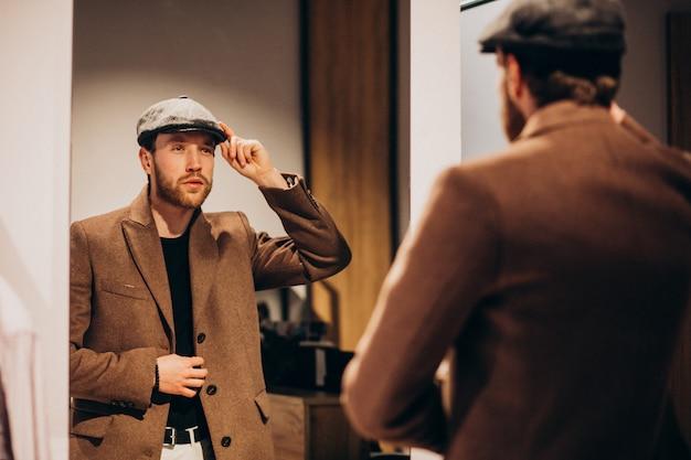 Hombre guapo joven que elige el sombrero en la tienda Foto gratis