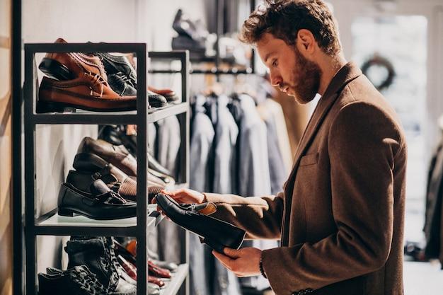 Hombre guapo joven que elige los zapatos en una tienda Foto gratis