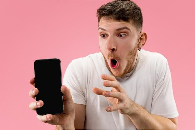 Hombre guapo joven que muestra la pantalla del teléfono inteligente sobre el espacio rosa con una cara de sorpresa Foto gratis