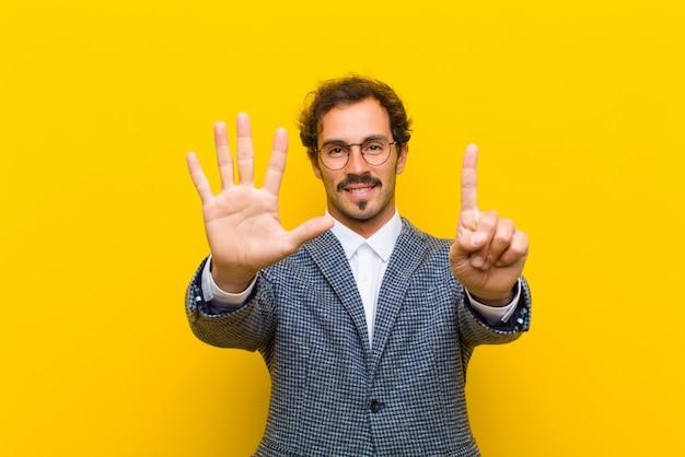 Hombre guapo joven sonriendo y mirando amigable, mostrando el número seis o sexto con la mano hacia adelante, contando contra naranja Foto Premium