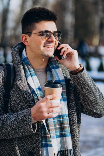 Hombre guapo joven tomando café fuera y usando el teléfono Foto gratis