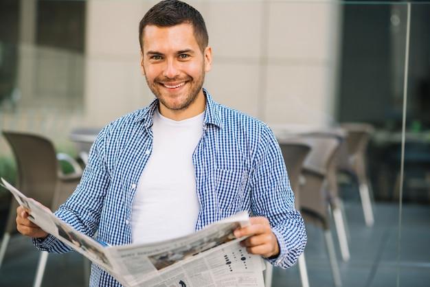 Hombre guapo leyendo periódico en café Foto gratis