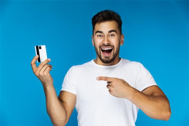 Hombre guapo muy emocional muestra su tarjeta de crédito Foto gratis