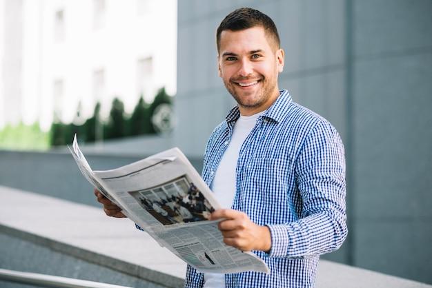 Hombre guapo con periódico Foto gratis