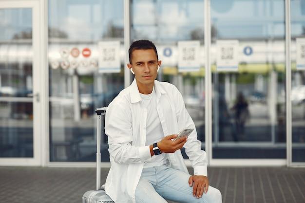 Hombre guapo de pie cerca del aeropuerto Foto gratis