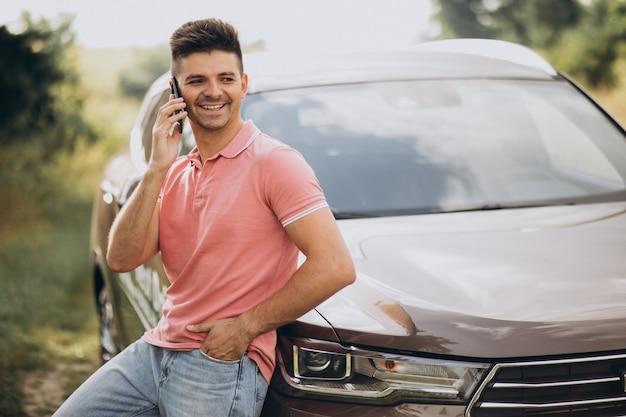 Hombre guapo de pie junto a su automóvil en el bosque Foto gratis