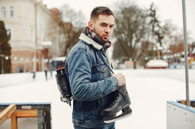 Hombre guapo en una pista de hielo con skate Foto gratis