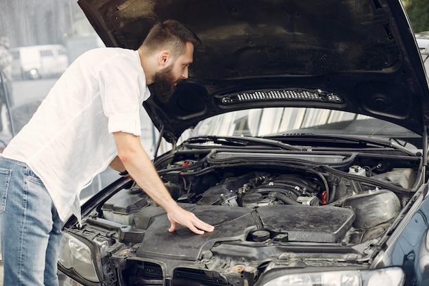 Hombre guapo revisa el motor de su auto Foto gratis