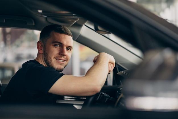 Hombre guapo sentado en el coche y probarlo Foto gratis