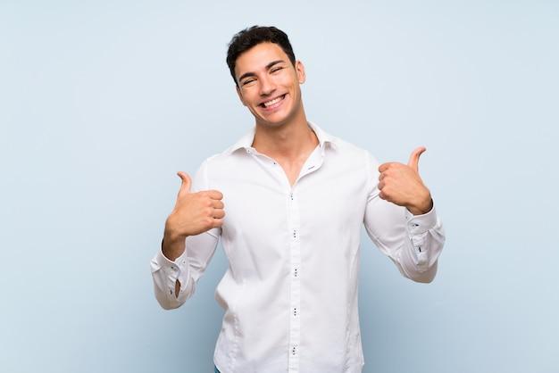 Hombre guapo sobre pared azul con pulgares arriba gesto y sonriendo Foto Premium