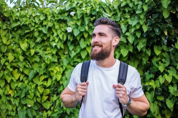 Hombre guapo sonriendo, con su mochila de aventura sobre un fondo de hojas verdes y naturales. Foto Premium