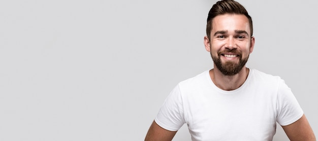 Hombre guapo sonriente en camiseta blanca con espacio de copia Foto Premium