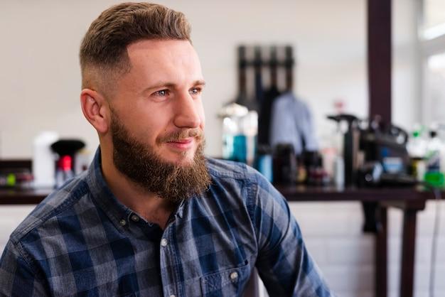 Hombre guapo sonriente en la peluquería Foto gratis