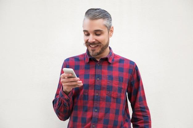 Hombre guapo sonriente con smartphone Foto gratis