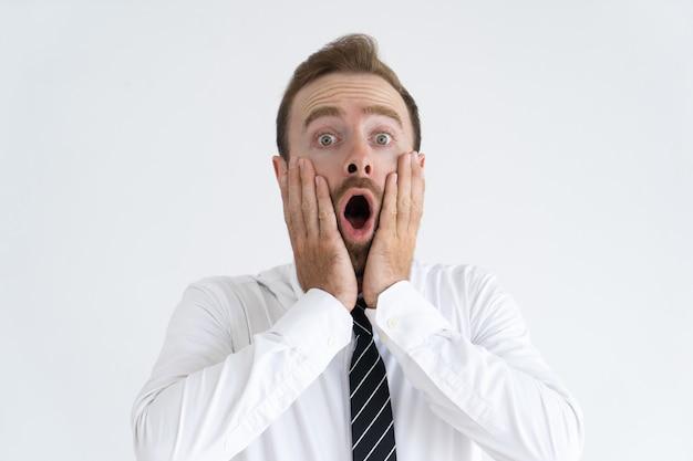 Hombre guapo sorprendido manteniendo la boca abierta y tocando las mejillas Foto gratis