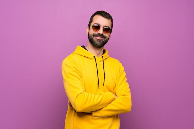 Hombre guapo con sudadera amarilla con gafas y sonriendo Foto Premium