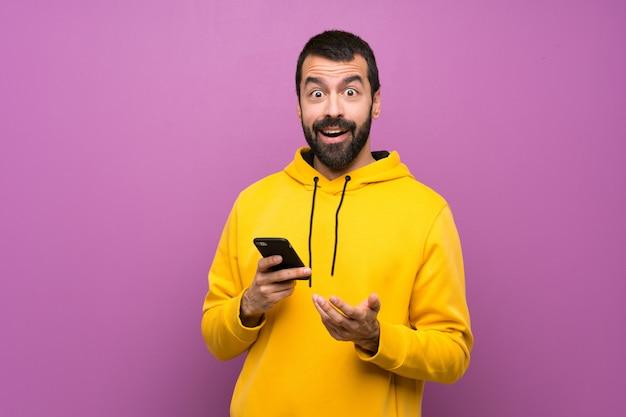 Hombre guapo con sudadera amarilla sorprendido y enviando un mensaje Foto Premium