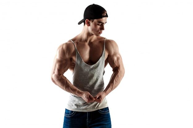 Hombre guapo súper alto musculoso en gorra de béisbol y camiseta sin mangas posando sobre fondo blanco Foto Premium