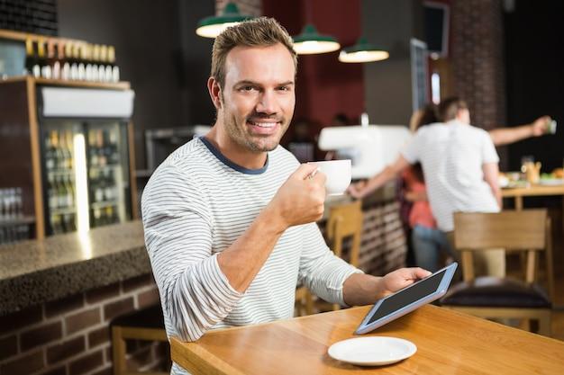 Hombre guapo con tableta y tomando un café Foto Premium