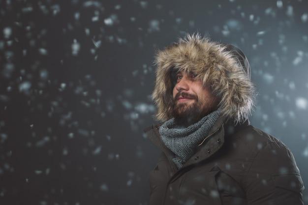 Hombre guapo en tormenta de nieve Foto gratis