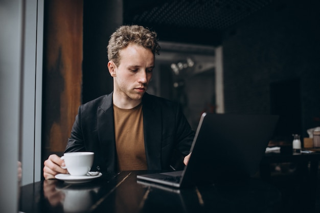 Hombre guapo trabajando en una computadora en un café y tomando café Foto gratis
