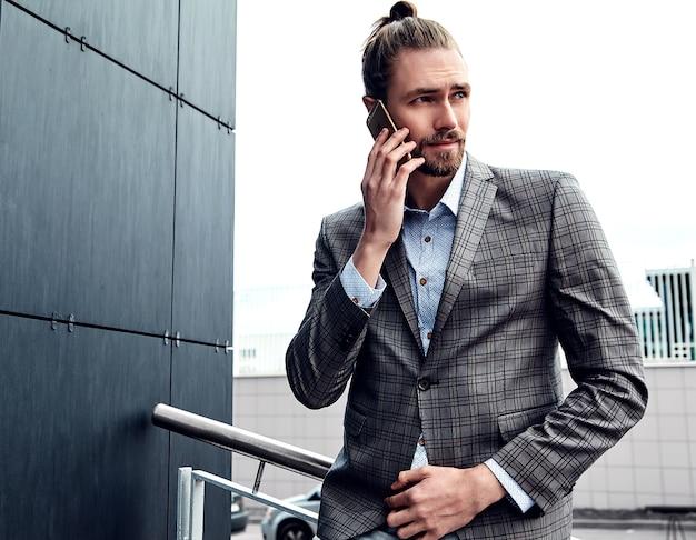 Hombre guapo en traje a cuadros gris hablando con teléfono inteligente Foto gratis