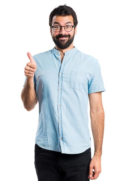 Hombre guapo con los vidrios azules con el pulgar para arriba Foto gratis