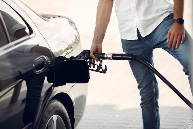Hombre guapo vierte gasolina en el tanque del automóvil Foto gratis