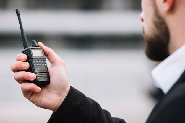 Hombre hablando a través de walkie talkie de seguridad Foto gratis