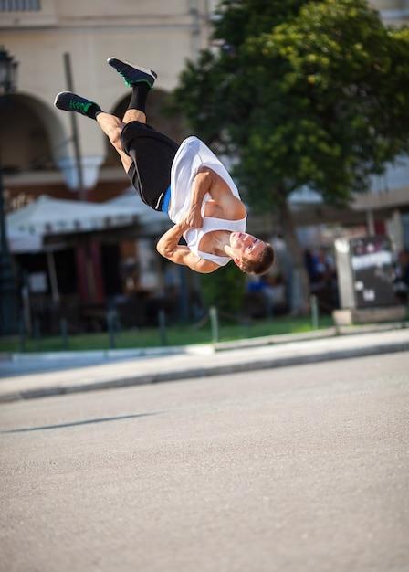 Hombre haciendo trucos acrobáticos en la calle de la ciudad Foto Premium