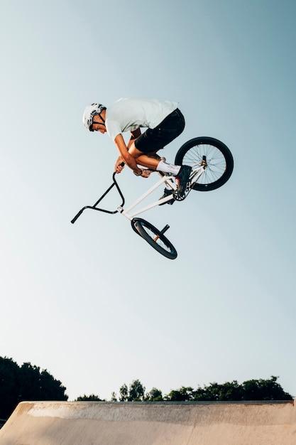 Hombre haciendo trucos al aire libre vista de ángulo bajo Foto gratis