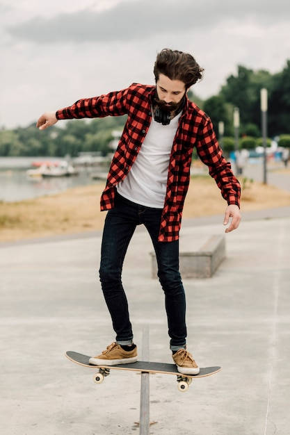 Hombre haciendo trucos con la patineta Foto gratis