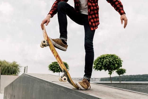 Hombre haciendo trucos de skate en el parque Foto gratis