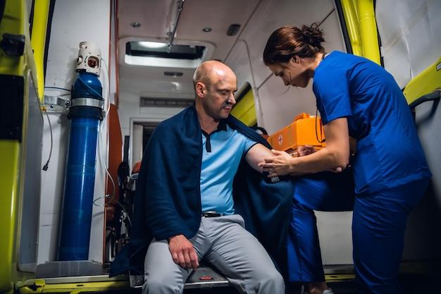Hombre herido en una manta está recibiendo primeros auxilios en una ambulancia Foto Premium
