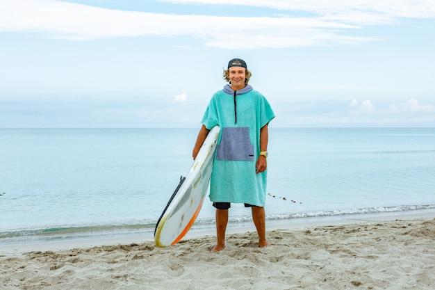 El hombre hermoso camina con la tabla de surf en blanco blanca espera la onda para surfear el lugar en la orilla del mar del océano. Foto Premium