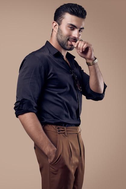 Hombre hermoso hipster bronceado brutal en una camisa negra y gafas Foto Premium