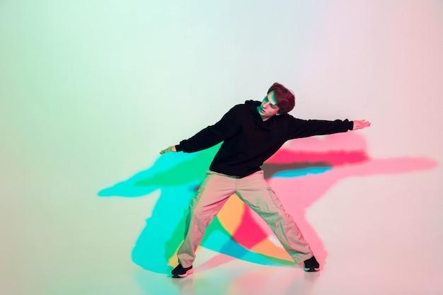 Hombre hermoso joven que baila hip-hop, estilo callejero aislado en estudio Foto gratis