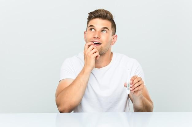 Hombre hermoso joven que sostiene un termómetro relajado pensando en algo mirando un espacio de copia. Foto Premium
