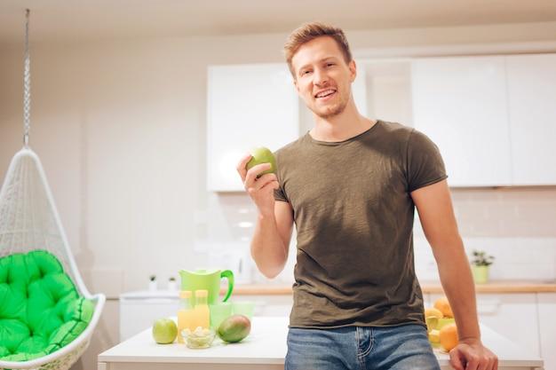 El hombre hermoso sonriente de los jóvenes sostiene la