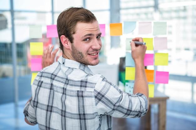 Hombre hipster escribiendo en post-it en la oficina Foto Premium