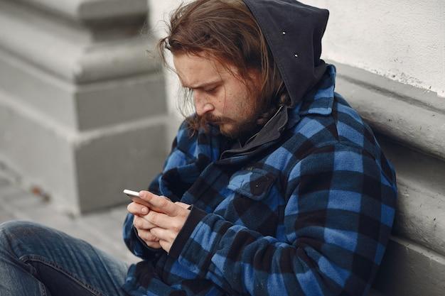 Hombre sin hogar en una ciudad durty ropa otoño Foto gratis