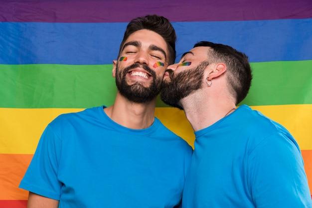 Hombre homosexual besando novio en bandera lgbt Foto gratis