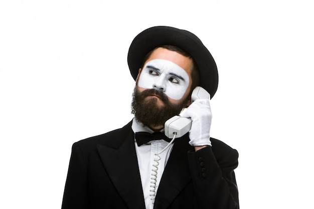 El hombre en la imagen imita sosteniendo un auricular. Foto gratis
