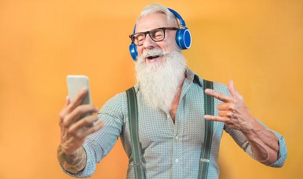 Hombre inconformista senior que usa la aplicación de teléfono inteligente para crear una lista de reproducción con música rock - tipo de tatuaje moderno que se divierte con la tecnología del teléfono móvil - tecnología y concepto alegre de estilo de vida para personas mayores - centrarse en la cara Foto Premium
