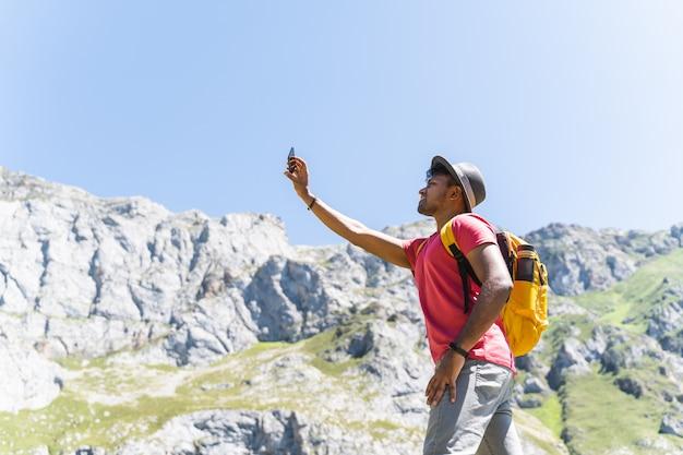Hombre indio llevando una mochila amarilla senderismo y tomar una foto a la montaña. Foto Premium