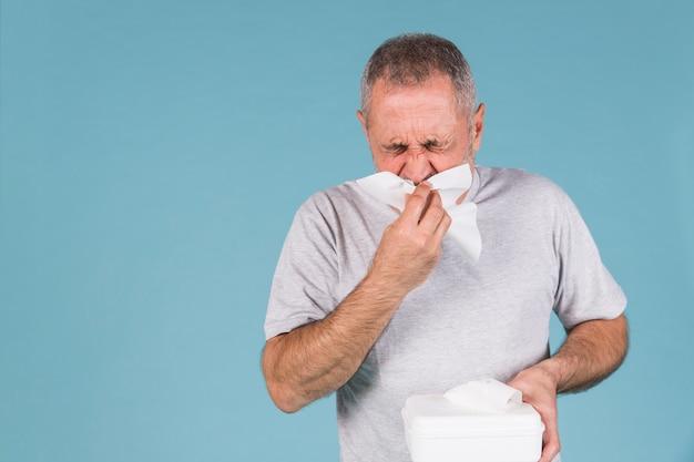 Hombre infectado con resfriado y gripe soplando su nariz en el tejido. Foto gratis