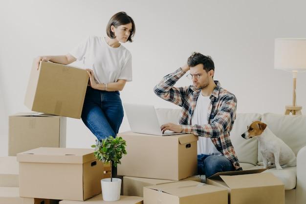 El hombre infeliz con gafas se sienta frente a una computadora portátil moderna, trabaja remotamente en casa Foto Premium
