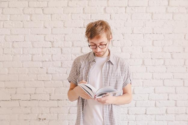 Hombre inteligente con gafas leyendo un libro Foto Premium
