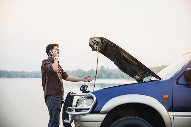El hombre intenta solucionar un problema con el motor de un automóvil en una carretera local chiang mai tailandia Foto gratis