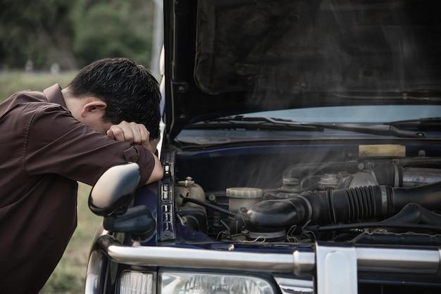 El hombre intenta solucionar un problema de motor de automóvil en una carretera local Foto gratis